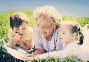 grandmother reading book to grandchildren